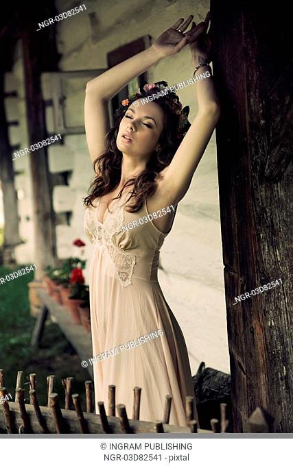 Sensual sexy lady posing next to the wooden house