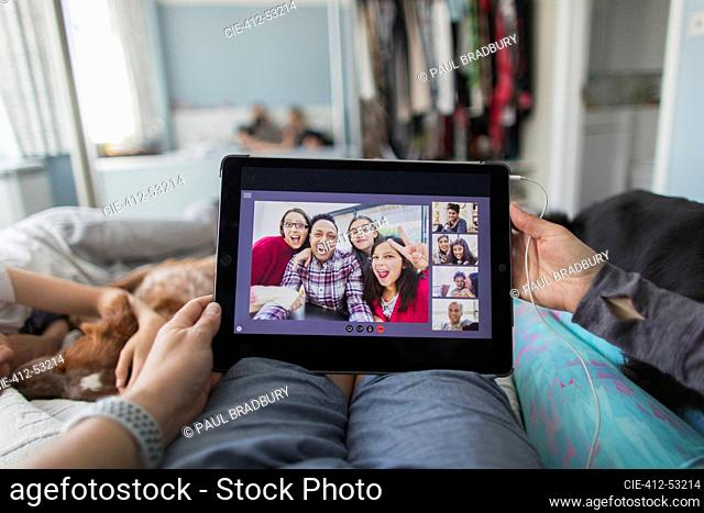 POV woman with digital tablet video chatting with friends on bed