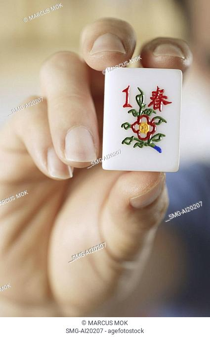 Close-up of hand holding mahjong tile with the Chinese script for Spring
