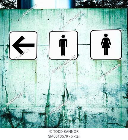 Men's and Women's restroom symbols with directional arrow. Pritzker Pavillion, Millennium Park Chicago, Illinois