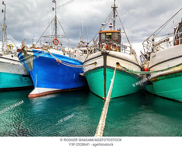 Fishing boats moored alongside one another as well as fore and aft, sheltering in a safe harbour before the arrival of a storm