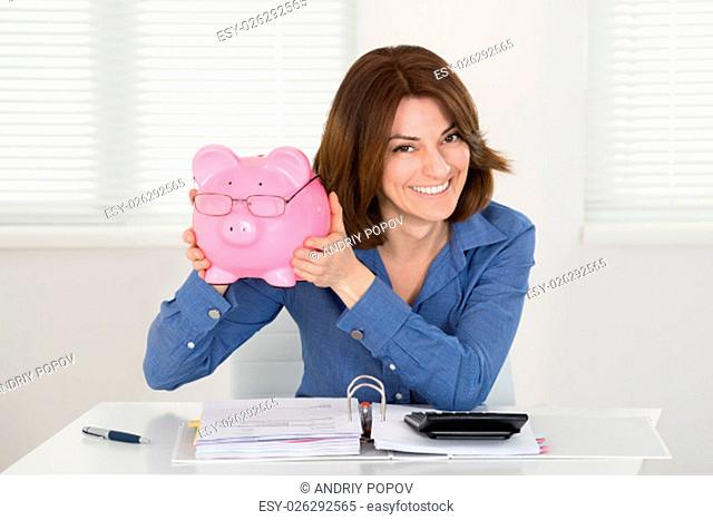 Happy Young Businesswoman Holding Piggybank With Document On Desk At Home