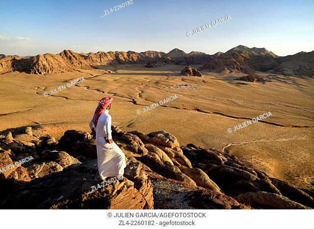 Bedouin and view from the mountain Jebel Khasch. Jordan, Wadi Rum desert, border with Saudi Arabia. Model Released