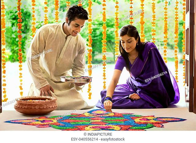 Couple making a rangoli