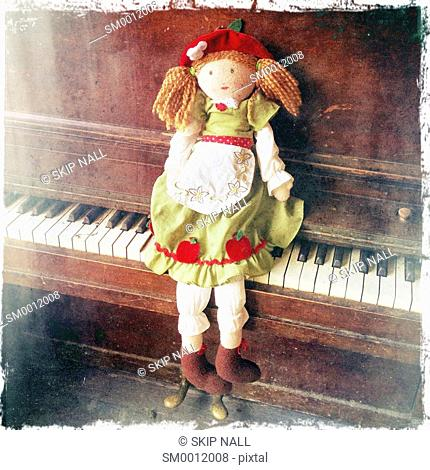 A rag doll sitting on the keys of a piano
