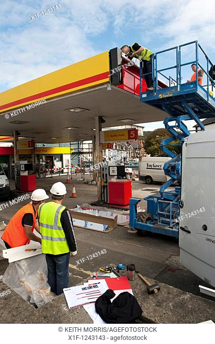 Workmen Renovating a Shell petrol station garage, UK