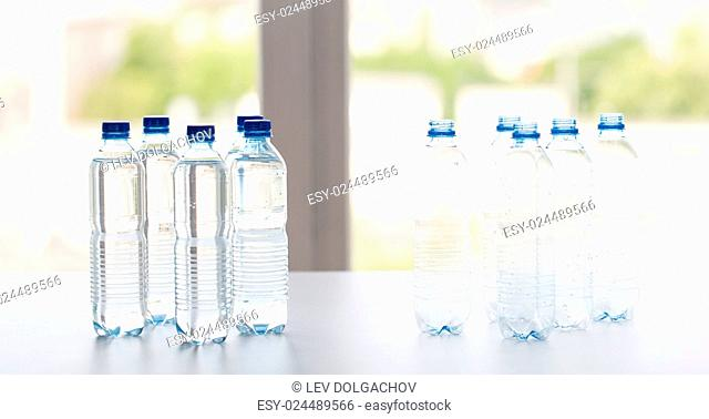 recycling, healthy eating and food storage concept - close up of plastic bottles with pure drinking water on table