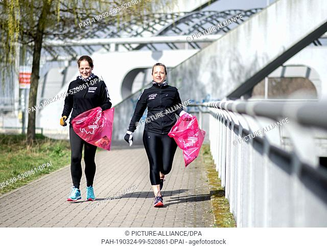 24 March 2019, Lower Saxony, Hannover: The joggers Denise (l) and Nicole collect garbage lying on the ground around the Noltemeyer Bridge in the Bothfeld...