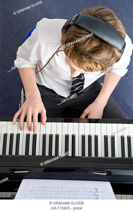 High school student with headphones playing piano