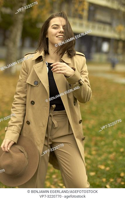 young playful woman walking outdoors in park during autumn season, wearing coat, prankish, coquettish, happy smiling, candid flirtatious emotion, in Munich