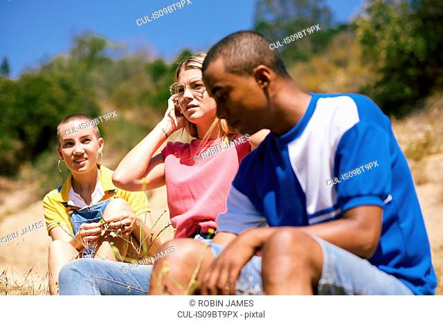 Three young adult friends sitting by dirt track, Los Angeles, California, USA