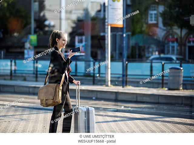 Smiling young woman with luggage at tram station in the city using cell phone