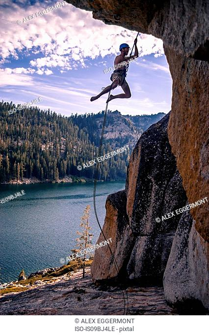 Young male rock climber dangling on rope from rock face, High Sierras, California, USA