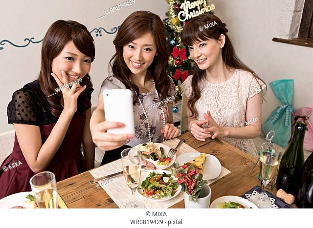 Three Young Women Taking Photograph with Smartphone at Christmas Party