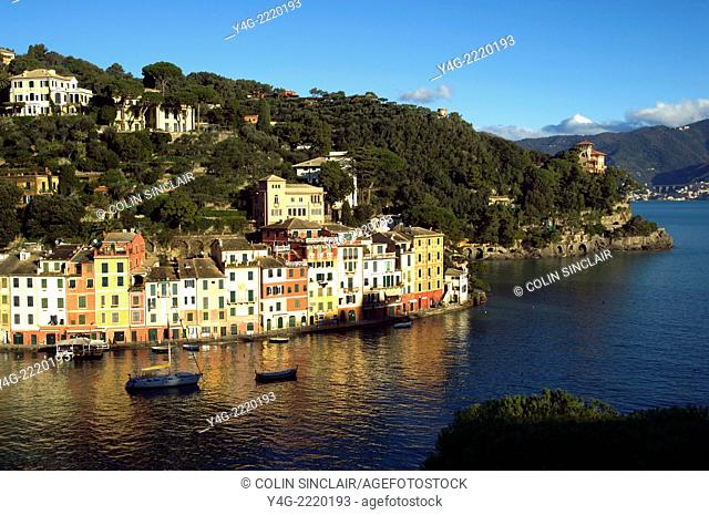 Portofino, Ligurian Coast, Italy, Port, Boats, Colourful homes, Reflections in Sea, Backdrop hillsides with pines and beautiful houses, Horizontal, Blue sky