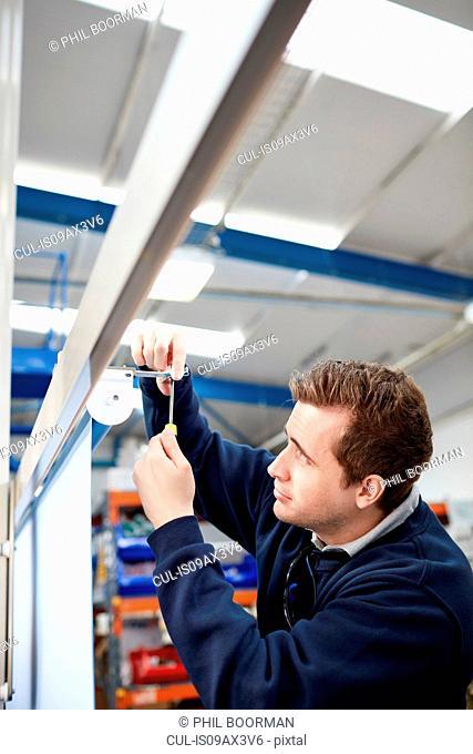 Male worker measuring roller blind in factory