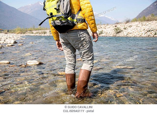 Cropped rear view of young male hiker crossing Toce river, Vogogna, Verbania, Piemonte, Italy