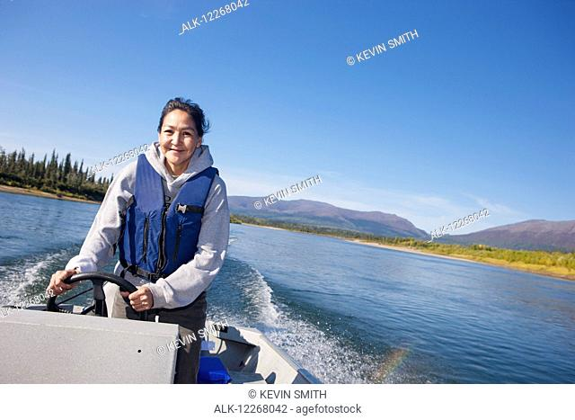 Alaskan Native female driving a motor boat on Kobuk river, Arctic Alaska, summer