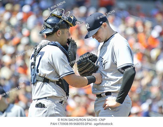 New York Yankees catcher Austin Romine (27), left, offers words of encouragement to starting pitcher Jordan Montgomery (47), right
