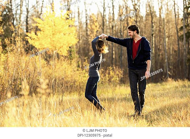 A young couple walking and pretending to dance in a city park in autumn; Edmonton, Alberta, Canada