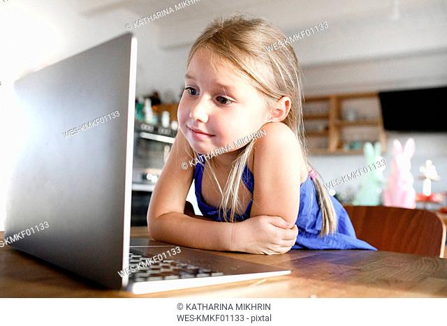 Portrait of little girl leaning on kitchen table at home looking at laptop