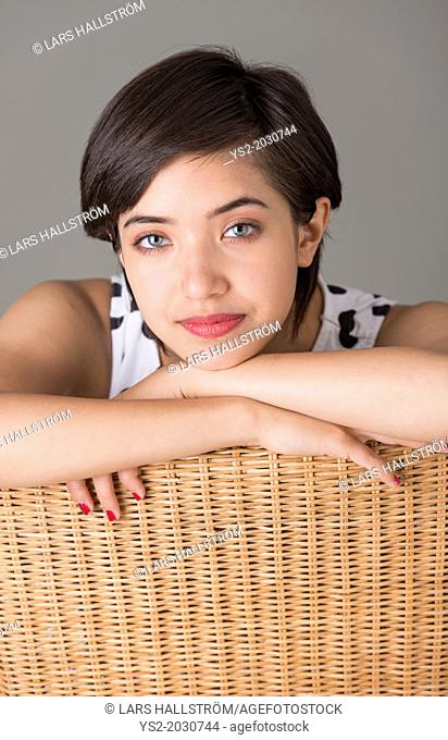 Young confident woman sitting in wicker chair looking at camera.1015
