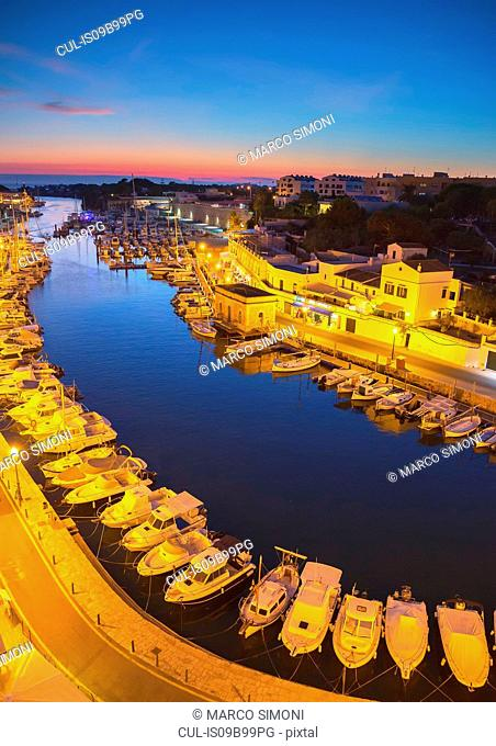 High angle view of historic harbour and rows of moored boats at dusk, Ciutadella, Menorca, Balearic Islands, Spain