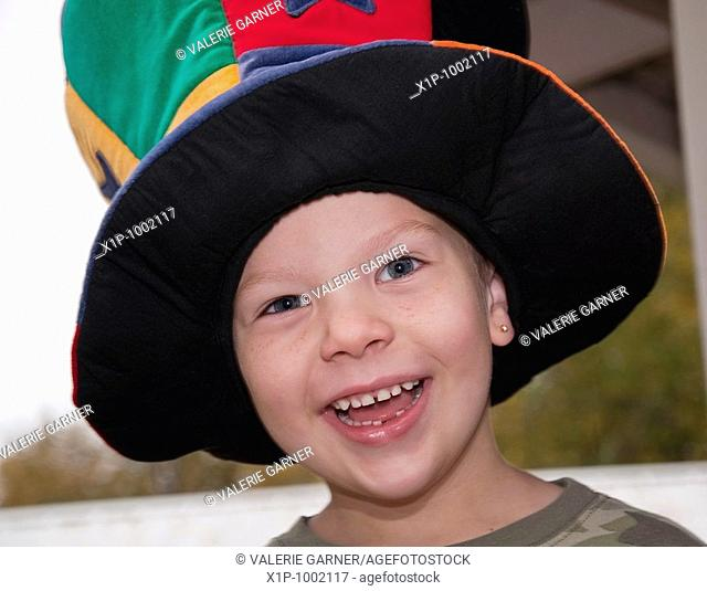 This cute 4 year old Caucasian boy with freckles and an earring is happy and smiling while wearing a colorful wacky hat Background is intentionally blurred for...