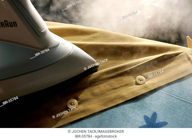 DEU, Germany : Iron of laundry at home. Steam iron