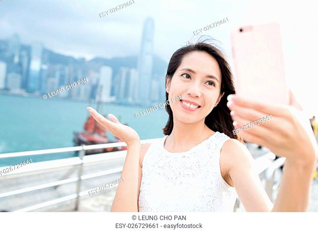 Woman taking picture by her self in Hong Kong