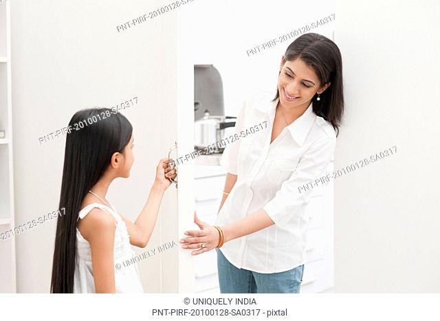 Woman and her daughter smiling near a door