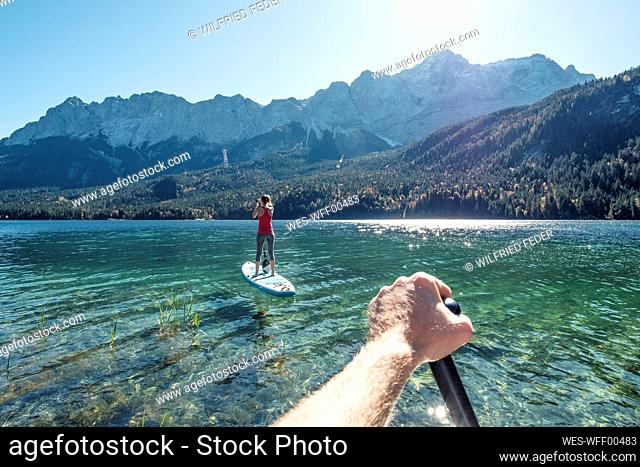 Germany, Bavaria, Garmisch Partenkirchen, Young couple stand up padling on Lake Eibsee, overlooking Zugspitze Mountain