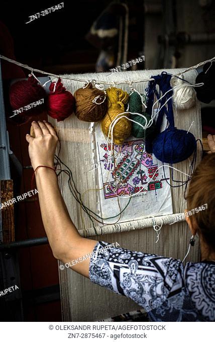 A woman weaves a carpet in a workshop of Quba, Azerbaijan. Quba school of carpet weaving is one of the most well-known in Azerbaijan