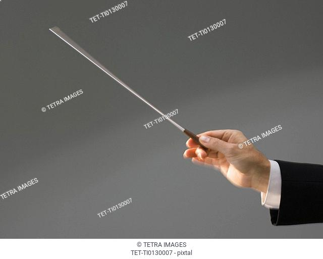 Male conductor's hand holding baton