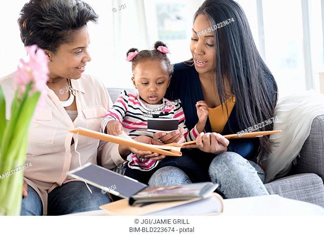 Black multi-generation family looking at photo album