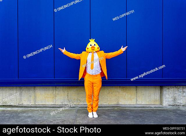 Man wearing vibrant orange suit and bird mask standing in front of blue wall with outstretched arms