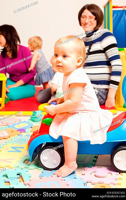 Baby on the car toy at the nursery