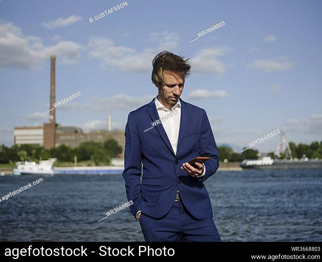 Male professional using mobile phone while standing against Rhine river during sunny day