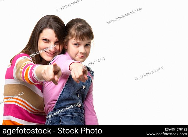 Mom and daughter point a finger at the frame, side empty space in the frame