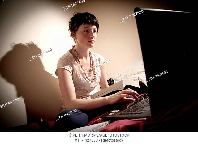 A young woman UK university student working on her laptop computer in her bedroom at home