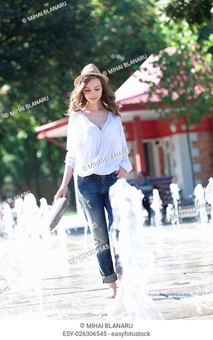 Lovely young woman playing with sparkling water in a park