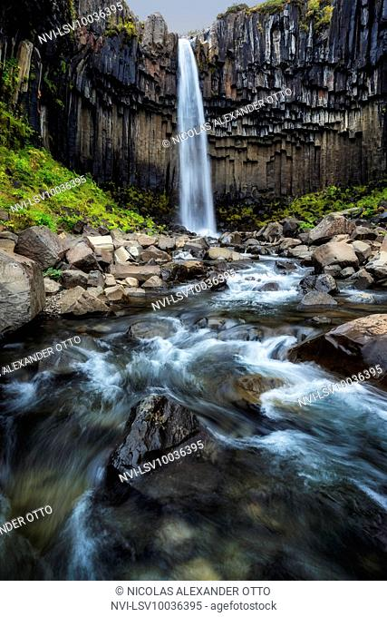 Svartifoss waterfall in autumn with watercourse in long exposure, Skaftafell National Park, Iceland