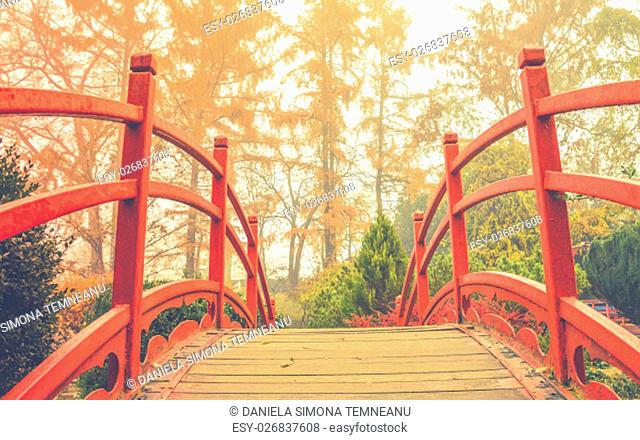 Wooden bridge with the red handrails in a japanese garden, against a background of autumnal trees
