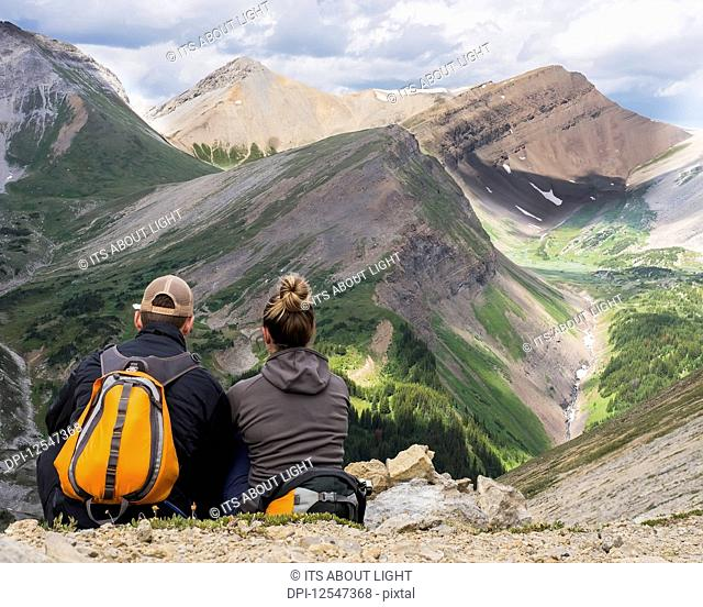 Male and female hiker sitting on a rock ridge overlooking a valley and mountain range in Kananaskis Country; Alberta, Canada