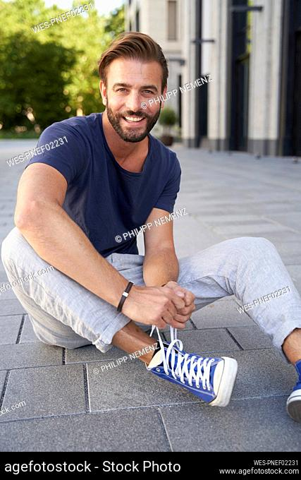 Portrait of smiling man sitting on the ground in the city lacing his shoes