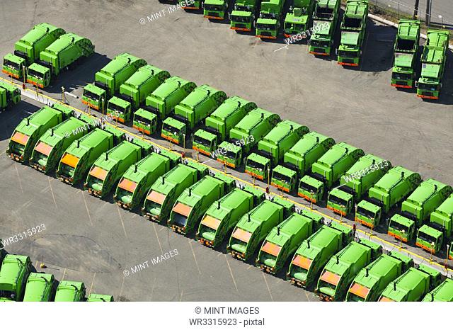 Aerial view of green garbage trucks in a row in parking lot
