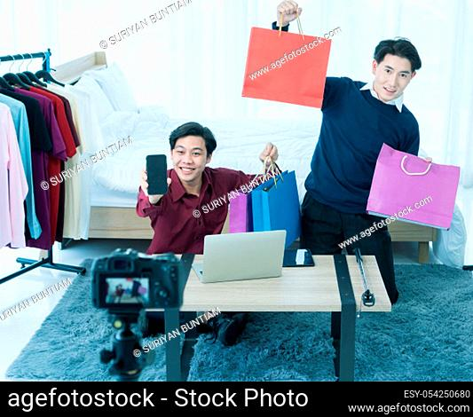 Two Asian men are having fun reviewing and selling products via live media via social media