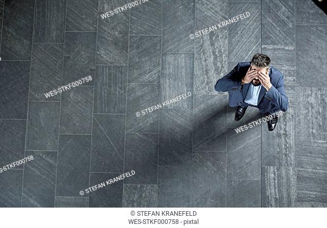 Germany, Neuss, Business man sitting cross-legged on table