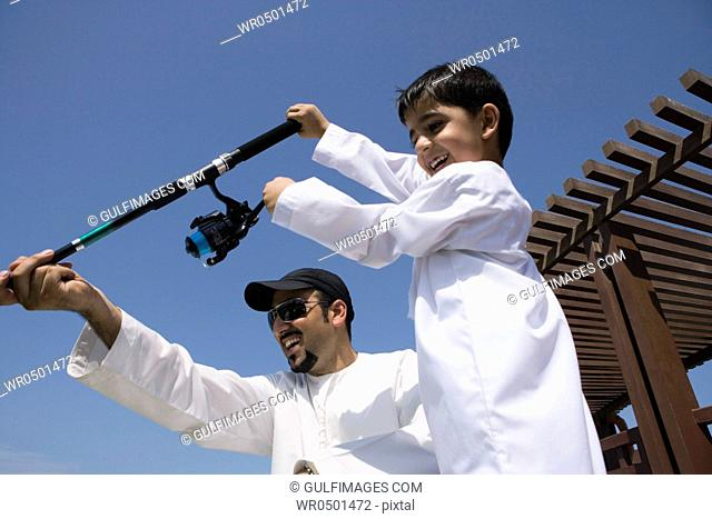 Father with son holding fishing rod, smiling, low angle view