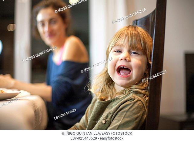 Three years old blonde child sitting at meal table with mother, looking at camera and speaking or shouting
